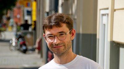 ein Mann mit Brille und Blick in die Kamera